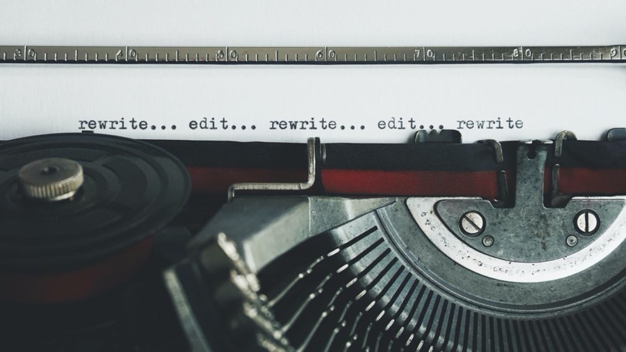 paper in typewriter with edit and rewrite typed